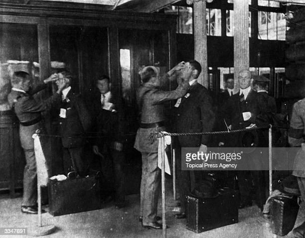 Immigrants to America undergo one of many medical tests at the immigration processing complex of Ellis Island in New York Bay