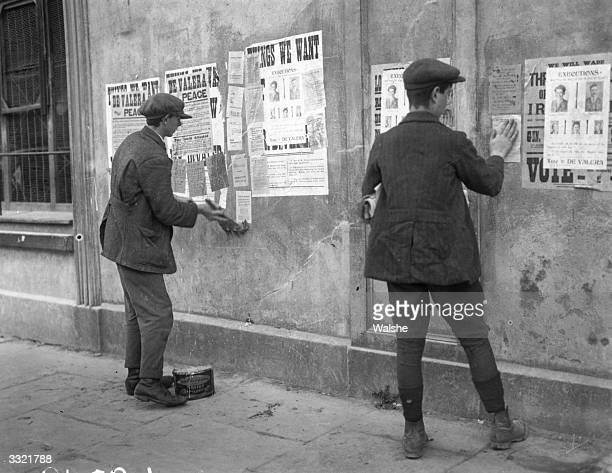 Men pasting up posters on the walls of the Election Committee Headquarters of Sinn Fein exhorting voters to vote for Sinn Fein leader Eamon de Valera...