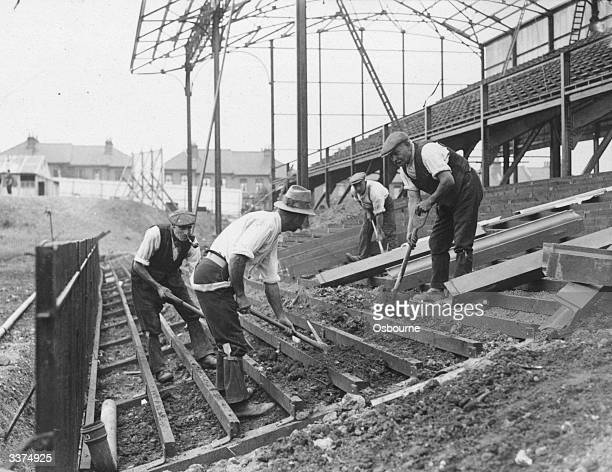 Men at work building terraces at Crystal Palace FC ground Norwood south London