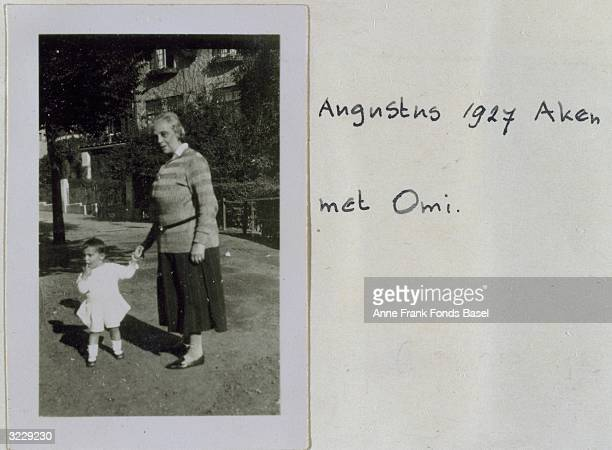 EXCLUSIVE Toddler Margot Frank the sister of Anne Frank stands holding her grandmother Alice's hand outdoors Aachen Germany Taken from Anne Frank's...