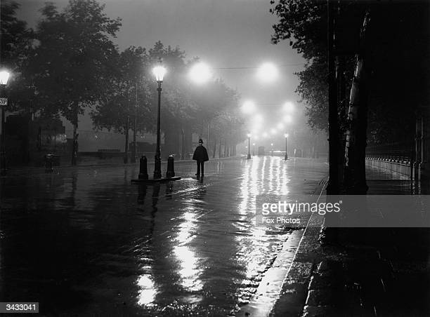 London policeman finds himself without any traffic to direct on a rainy night on the River Thames Embankment between Chelsea and Westminster.