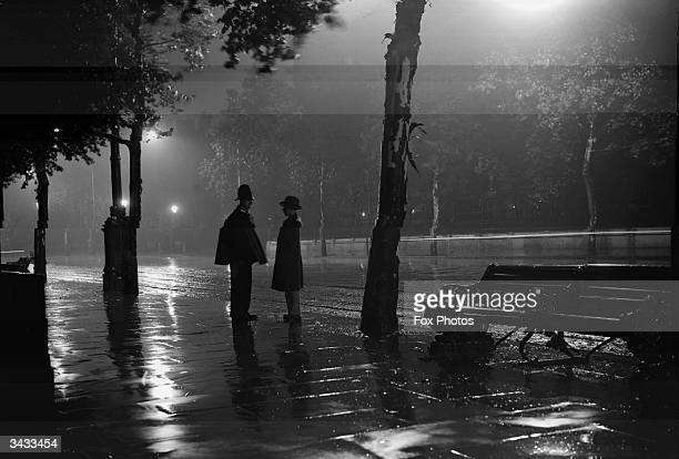 A man stops to talk to a lone policeman standing in the rain on the River Thames Embankment