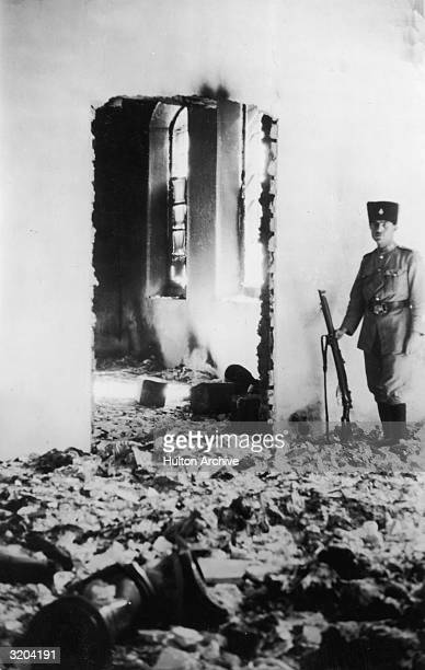 A soldier standing guard in the ruins of a Jewish hospital in Hebron after it was pillaged by Arabs