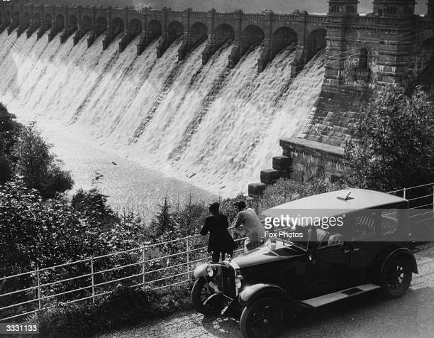 Two men have got out of their car to view the water pouring through the sluice gates in Lake Vyrnwy Dam North Wales