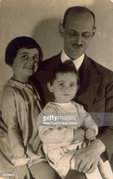 EXCLUSIVE A portrait of Anne Frank and her sister Margot Frank sitting on their father Otto Frank's lap Frankfurt am Main Germany From Anne Frank's...
