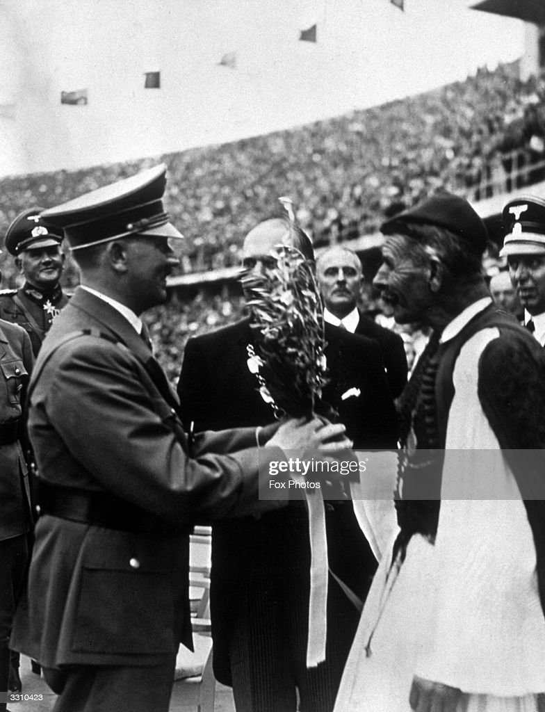 Adolf Hitler receiving the Olympic olive branch from Greek athlete Spyridon Louis, winner of the 1896 marathon, at the 1936 Berlin Olympics.