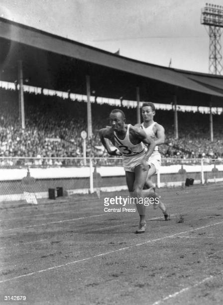 American athlete Jesse Owens takes over from M Glickman in the 400 yards relay in a USA versus British Empire meeting at White City stadium in west...