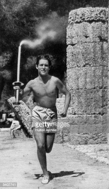 Constantine Kondyllis carries the Olympic Torch over the first part of the 3000km stretch from Olympia to Berlin for the start of the 1936 Olympic...