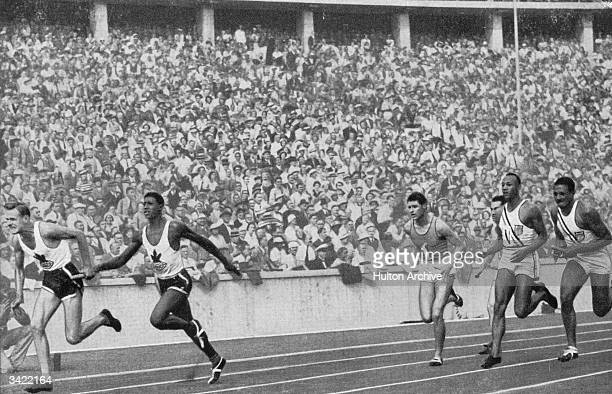 Jesse Owens in lane four hands over the baton to Ralph Metcalfe in the 4 x 100 metres relay race final at the 1936 Berlin Olympic games The American...