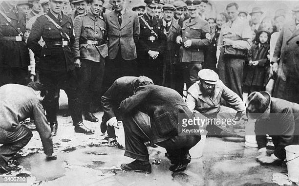 Young German officers watching a group of elderly Jewish men scrubbing the streets of Vienna