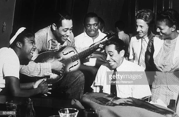 American composer and bandleader Duke Ellington plays guitar and Cab Calloway plays piano during a jam session at a private party hosted by Hearst...