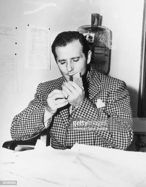 American mobster Benjamin 'Bugsy' Siegel lighting a cigar