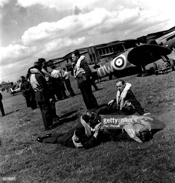 Pilots of No 610 'County of Chester' Squadron Royal Auxiliary Air Force resting and talking around their Supermarine Spitfire I fighters on Hawkinge...