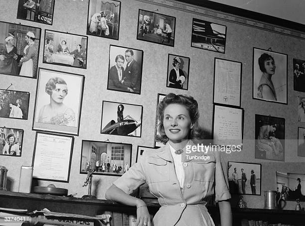 English actress Ann Todd at home with a collection of photographs and memorabilia from her film career