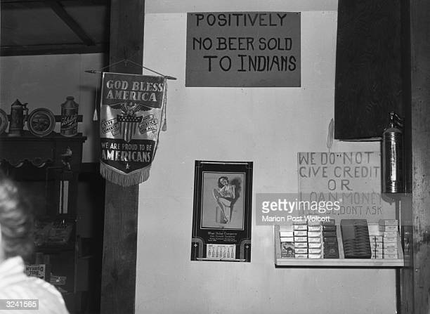 View of a barroom wall showing a patriotic banner next to a sign refusing the business of Indians and a calendar featuring a pinup girl Birney...