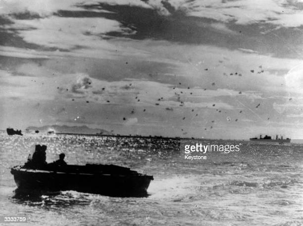 Anti aircraft fire, sent up by US warships as protection for their forces who are landing on the beaches at Guadalcanal, can be seen as black dots in...