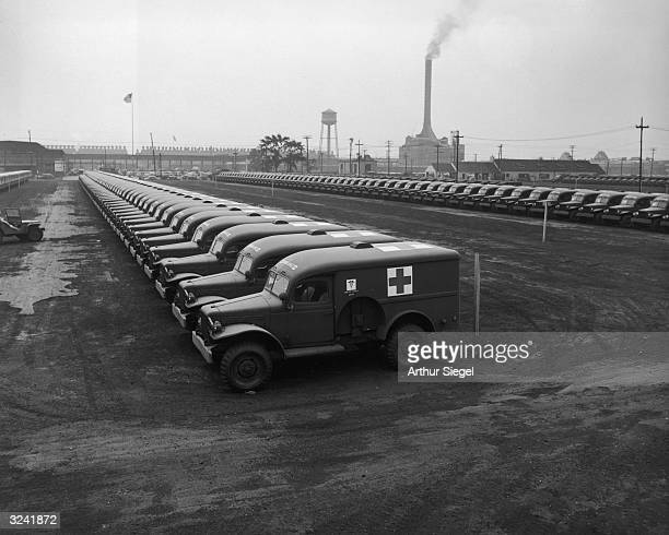 Rows of army ambulances sit in a parking lot at a Chrysler corporation Dodge truck plant Detroit Michigan World War II
