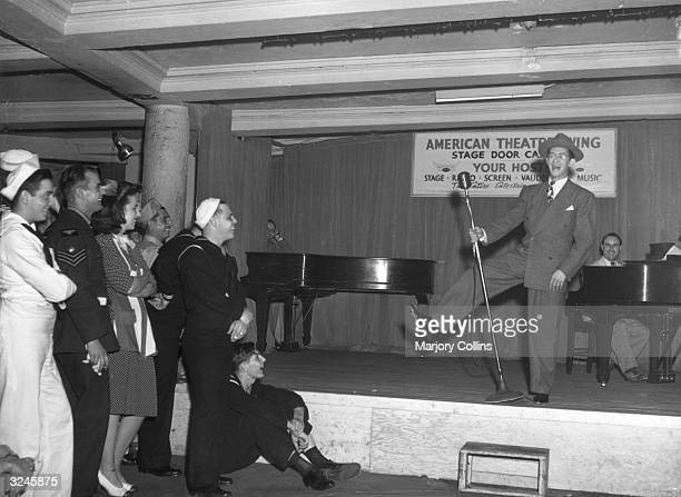 An unidentified male entertainer performs on stage for an audience of American military personnel at the Stage Door Canteen, New York City.