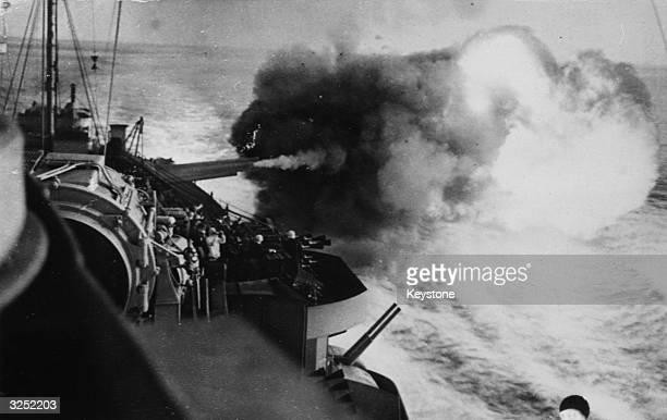The guns of a British battleship firing shells at a range of 11,000 - 15,000 yards on enemy ships, still holding out at Catania, Sicily.