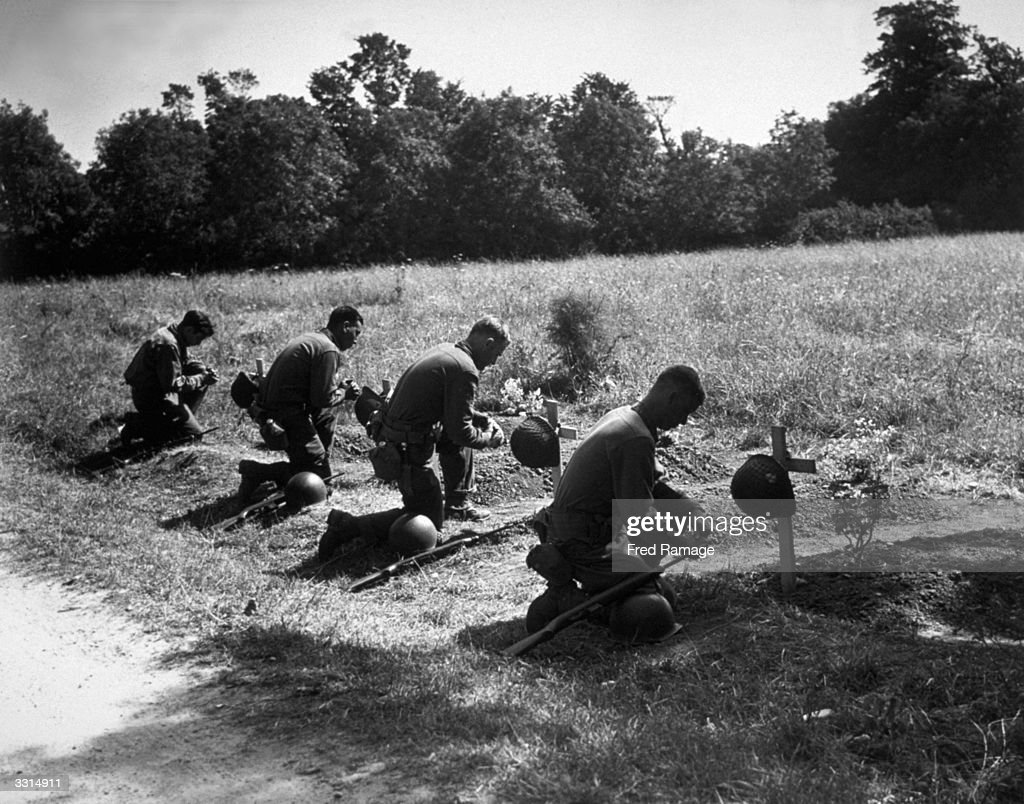 American soldiers kneel in homage at the graves of their dead comrades near Sainte Mere Eglise.