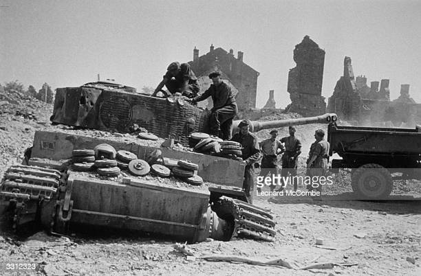 British Engineers fill the wreck of a German Tiger 1E tank with landmines in order to destroy it after the allies recaptured the village of...