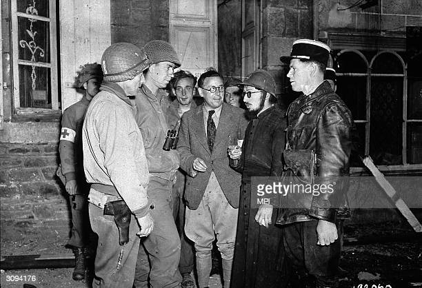 During the liberation of Paris in WW II GIs and French gendarmes confer with partisans