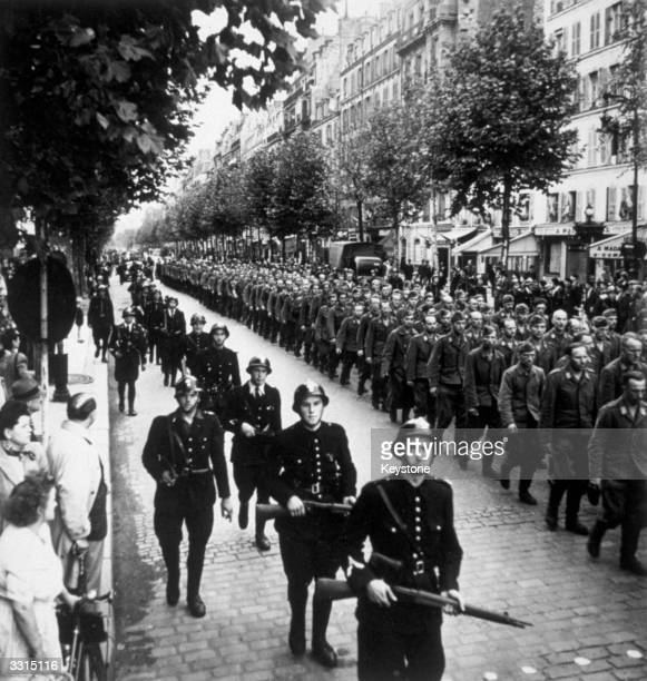 Guarded by the French police German prisoners march through the streets of liberated Paris on their way to a POW camp Paris was liberated on 25th...