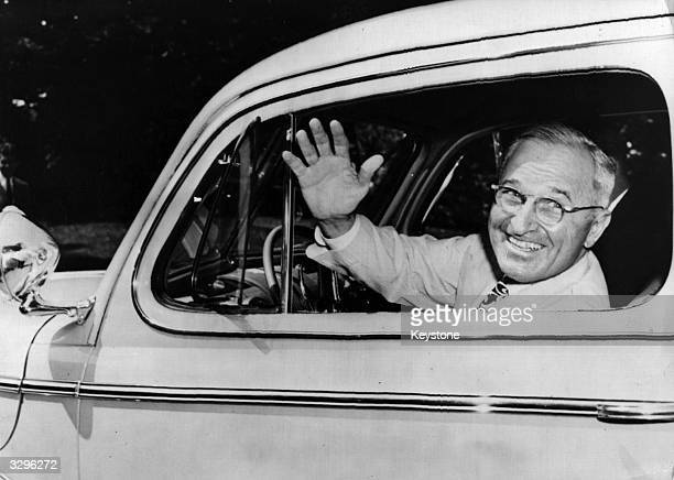 The 33rd President of the United States of America Harry S Truman at the wheel of his new beigecoloured 1945 de luxe twodoor Ford sedan a present...