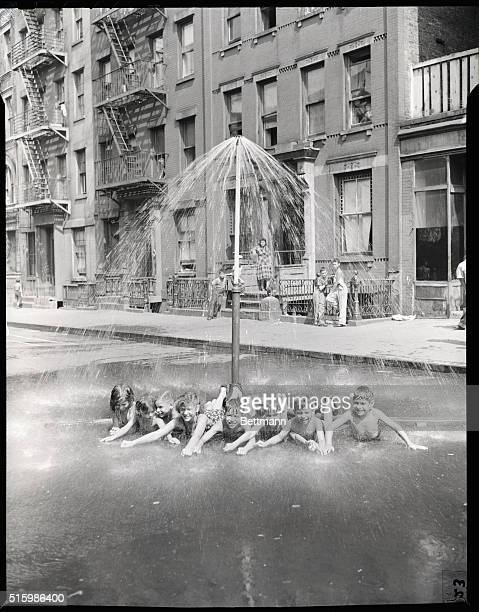 August 1948 Children under a shower on a play street in Spanish town East 101 St Near Lexington Ave This is the Spanish and Puerto Rican section of...