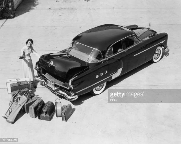 Woman demonstrates the trunk capacity of the 1951 Packard Patrician 400.