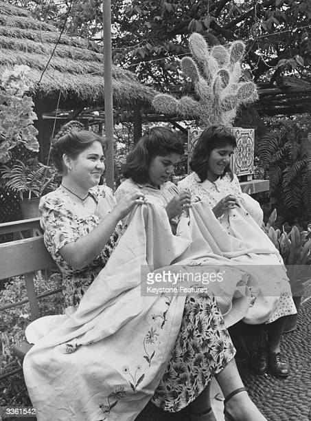 Three women on the island of Madeira embroider a tablecloth that will eventually be exported