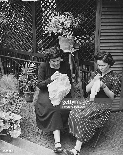 Women from the island of Madeira sit on the verandah of their home busy with embroidery work