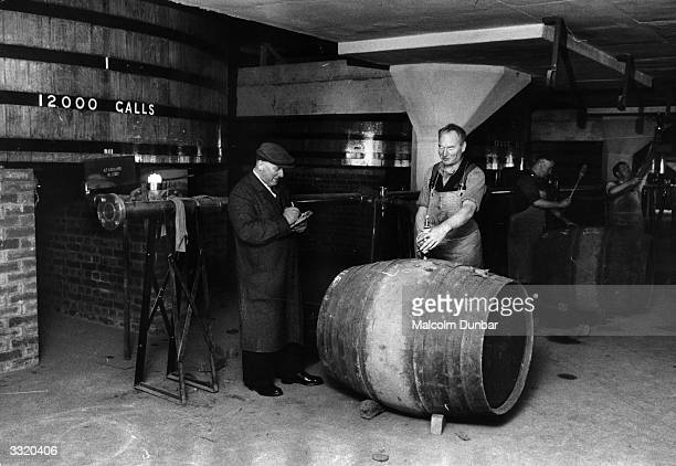 Workers at the blending and bottling warehouse of the Distillers' Agency Ltd Glasgow inspecting a barrel of whisky Scottish whisky is first mentioned...