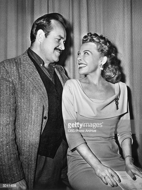 Promotional photo of American actors William Conrad and Georgia Ellis smiling at each other during a break from rehearsal of the Western drama radio...