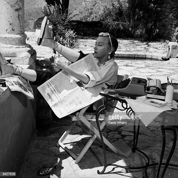 Silent screen star Gloria Swanson lounges with a typewriter on the verandah of her house near Nice on the French Riviera Although she continued to...