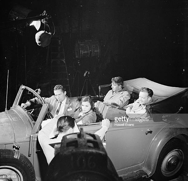 Actors Eva Bartok Peter Finch Tony Britton and Alexander Knox in an old Mercedes at Pinewood Studios filming the Michael McCarthy picture 'Operation...