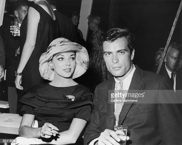 Britishborn actor Joan Collins smokes a cigarette and American actor and artist Gardner McKay holds a drink as they sit together during a party...