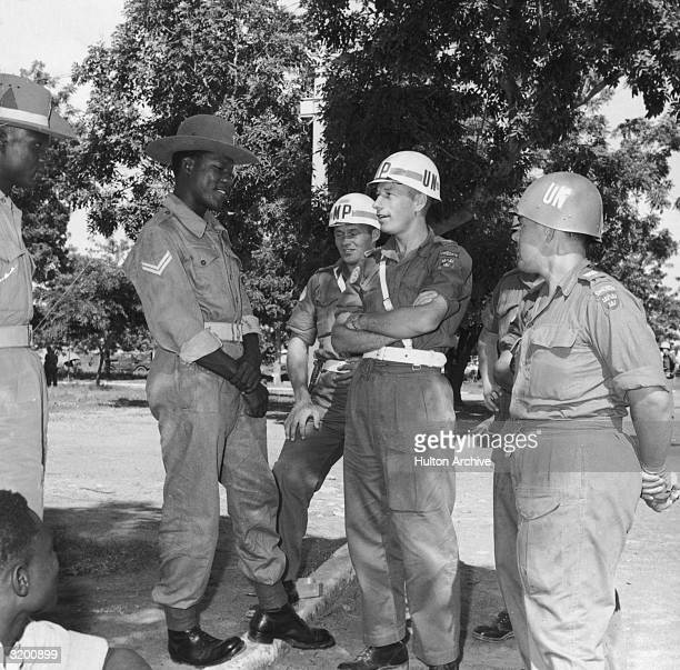 Swedish troops, part of the United Nations peacekeeping forces in the Republic of Congo, stand talking with Nigerian soldiers at Kano airport,...