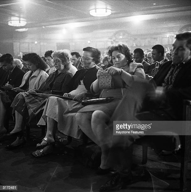 A woman looks for something to calm the nerves as expectation rises during a game of bingo in the Trocadero Cinema at the Elephant and Castle London