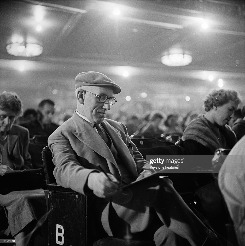 An old man ticks of his numbers as they are called for a game of bingo in the Trocadero Cinema at the Elephant and Castle, London.