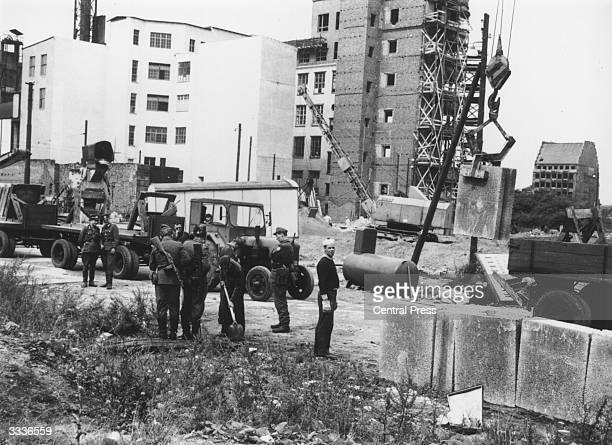 East German military personnel supervising construction of the Berlin Wall