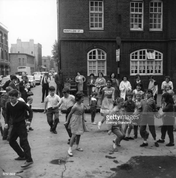 A group of schoolchildren dance the 'Twist' during their playbreak in Shoreditch East London