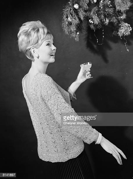 A woman in a pretty knitted jersey enjoys a festive drink under the Christmas wreath