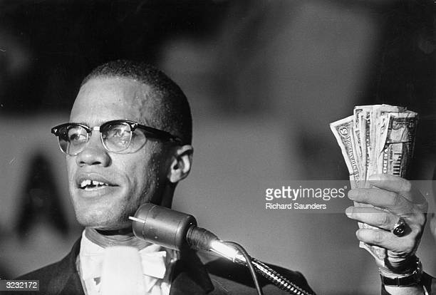 Headshot of American political activist Malcolm X holding a fist full of US currency during a speech at Urline Arena Washington DC