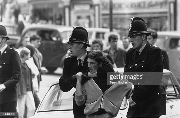 Policemen 'removing' a troublemaker during a clash between 'Mods' and 'Rockers' in Margate Kent