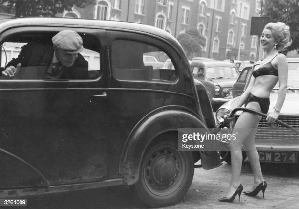 A driver at the head of a queue of cars casts a look back at bikiniclad Mari Rennie as she serves his car a free gallon of petrol as a gimmick to...