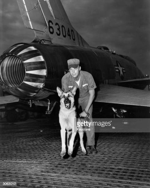 American airman Clifford Davies and his guard dog Dutchess standing guard on the flight line at Tan Son Nhut Air Base in Vietnam