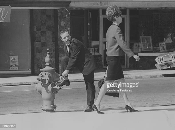 A member of the International Society of Girl Watchers uses the ploy of tying his shoelace in order to leer unnoticed at a passing woman Founded in...