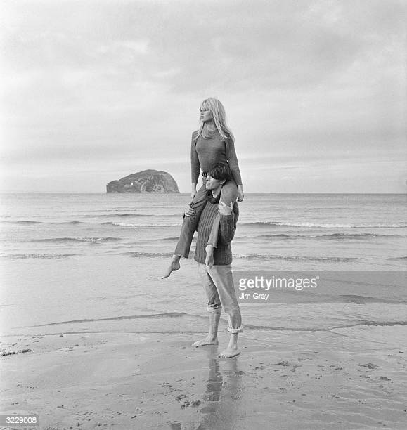 French actor Laurent Terzieff giving Brigitte Bardot a piggyback ride on the windy beach at North Berwick Scotland in a scene from the film 'Two...