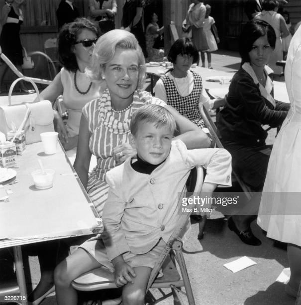 Kay Gable widow of actor Clark Gable with their son John Clark at a children's party a 'Batman' luncheon for an orphanage California August 1966